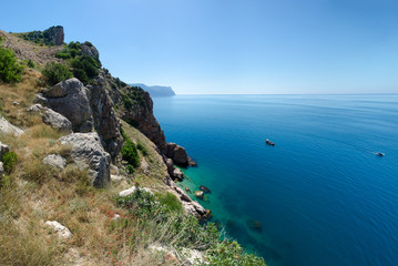 Rocky shore coast of tropical azure sea. The Black Sea, Crimea. Hot, sunny summer day