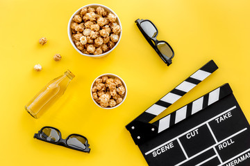 Snacks for film watching. Popcorn and soda near clapperboard, glasses on yellow background top view