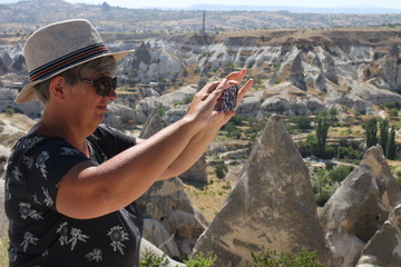 An English lady tourist taking pictures of the fairy chimneys in goreme, cappadocia in turkey 2017