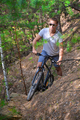 A cyclist rides a mountain bike on rough terrain. A young athlete. Taking sports in nature. Healthy way of life