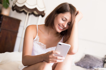 Chatting with boyfriend. Attractive young woman using smart phone and keeping hand in hair while sitting on the bed at home