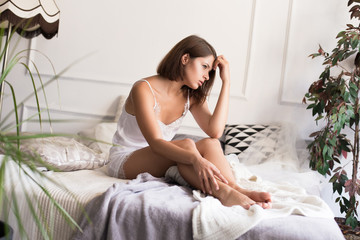 Headache. A young woman sitting on the bed at home, puts his hand to the head.