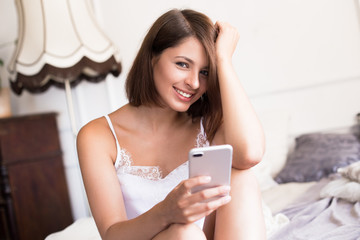 Sincere smile. Close up of attractive young woman using smart phone and smiling while sitting on the bed at home looking at the camera