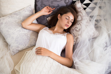 Sleeping angel. Top view of attractive young woman keeping eyes closed while stretching in the bed at home