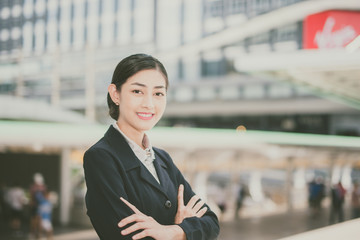 Modern Asian business woman standing outdoors with office building in the background copy space vintage tone