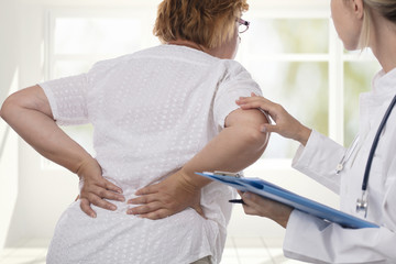 Senior woman with back pain. Osteopathy, Alternative medicine, pain relief concept. Physiotherapy, sport injury rehabilitation