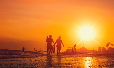 happy family and tourist silhouettes on the beach during sunsetin summer