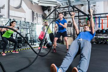 Männer und Frauen beim Crossfit Training im Fitnessstudio treiben Sport an Ringen und Seil