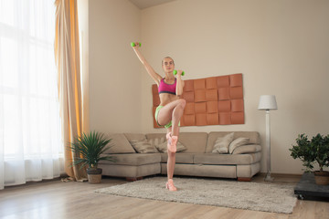 young blonde female doing aerobics with dumbbells exercise at home interior