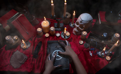 Witchcraft composition with witch's hands, satanic magic books, skull, candles, tarot cards, crystal and amulets. Halloween and occult concept, black magic ritual.