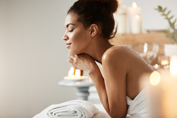 Portrait of pleased african girl relaxing with closed eyes in spa salon.