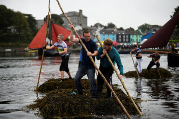 Teams approach the finish line of a seaweed race pushing a two tonne seaweed bundles known as Climin from the sea to the harbour finish line during Cruinniu na mBad regatta in Kinvara