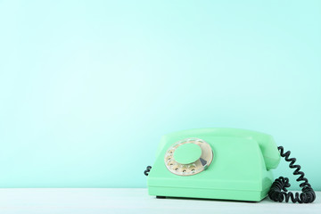 Green retro telephone on white wooden table