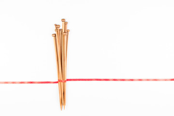 Wooden knitting needles and red and white polka dot ribbon on white background as frame