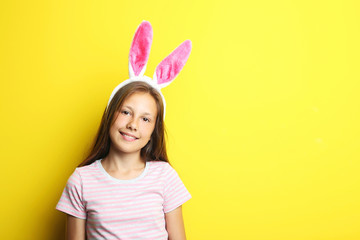 Portrait of beautiful girl with rabbit ears on yellow background
