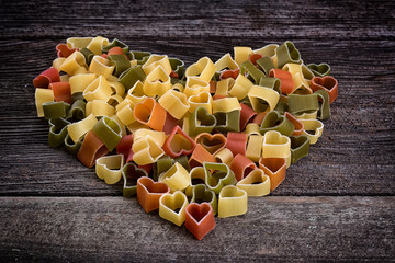 Italian pasta in the shape of a heart on a wooden background overhead shot