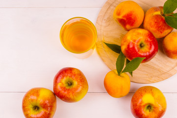 Glass of juice and ripe apples and peaches on a wooden table. Juice and fresh fruits on a light background. Copy Space