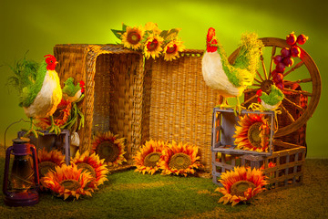 Decoration of the farm. Roosters are sitting on wicker baskets. Rustic utensils.