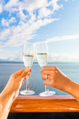 Luxury honeymoon cruise couple toasting champagne. Travel holiday newlyweds drinking with wedding rings holding glasses doing cheers at sunset view of cruise holiday destination.