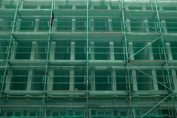 Ein mit grünem Netz abgesichertes Baustellengerüst