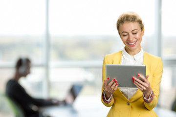 Smiling business lady with pc tablet. Cheerful young business woman looking on computer tablet and smiling, office window background.