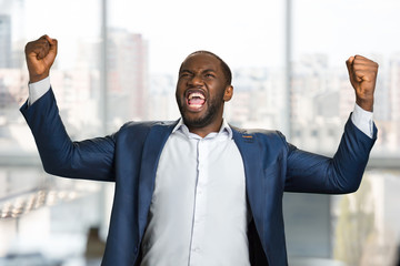 Excited black entrepreneur clenching his fists. Shouting with joyful young entrepreneur raised hands. Expression of goal achievement with raised arms.