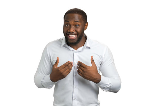 Smiling man pointing at himself with two hands. Afro american man in white shirt with a questioning look and a smile pointing at himself. Are you laughing? Of course I can!