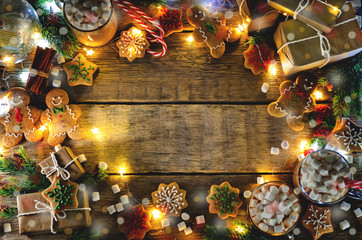 Dark wooden background with cocoa, gingerbread cookies, Christmas trees and gifts