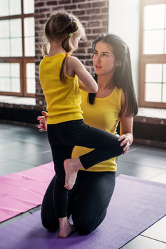 Kids yoga teacher teaching a girl child doing balance one-legged tree pose in gym