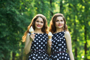 Two girlfriends sister twins of the same appearance with makeup and hairdo in the summer park eating ice cream