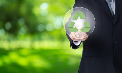 business man finger pointing at paper green recycle symbol with nature background, environment concept.