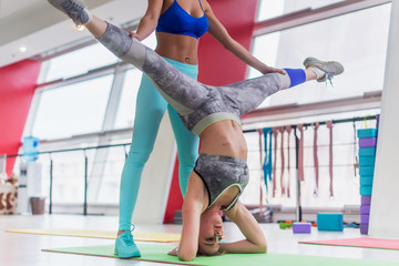 Fit young woman performing yoga headstand leg split with the help of a personal trainer in sports club.
