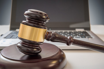 Gavel and laptop in background. Internet security and laws concept.