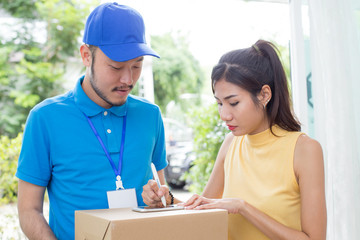 Young Asian Woman receive Box from  Delivery Man and Sign on Smartphone. People with Delivery Concept.