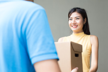 Young Asian Woman receive Box from  Delivery Man with Attractive Smiling at Home. People with Delivery Concept.
