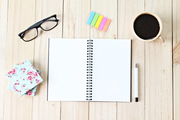 Still life business office supplies or education concept  Top view of working desk with blank notebook with pen, coffee cup, colorful note pad and eyeglasses on wooden background