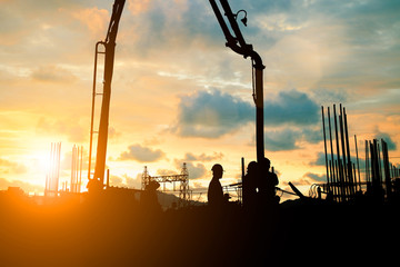 Silhouette construction industry team safely to work load concrete building according to set goal over blurred background sunset pastel for industry background.with Light fair