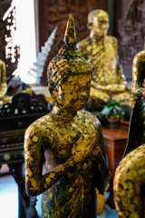 Old standing buddha image statue with Friday posture covered by gold leaf, Asokaram temple
