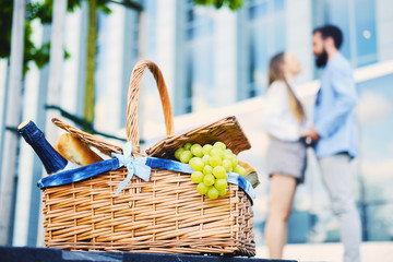 A picnic basket full of fruits, bread and wine.