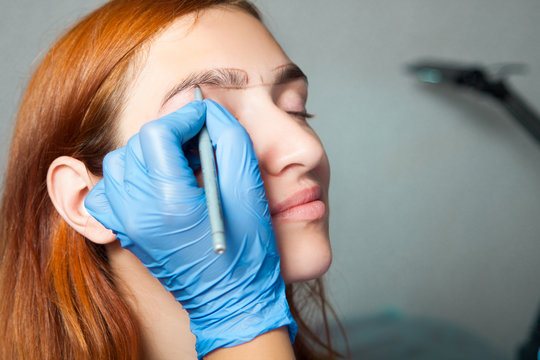 The master on the eyebrows draws the shape of the grafted eyebrow shape in a blue medical disposable gloves red-haired beautiful woman on a gray background