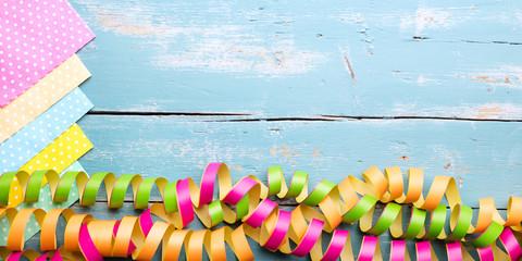 Bunte Servietten und Luftschlangen auf Holz mit Textfreiraum