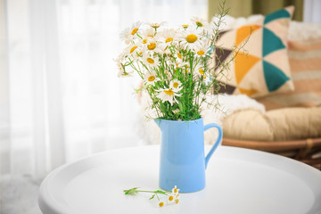 Beautiful bouquet of chamomile flowers in jug on table