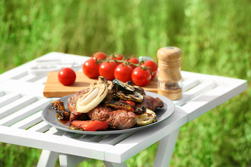Wall Mural - Grilled tasty beefsteaks and vegetables on white table outdoors