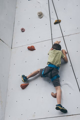 little boy climbing a rock wall outdoor.