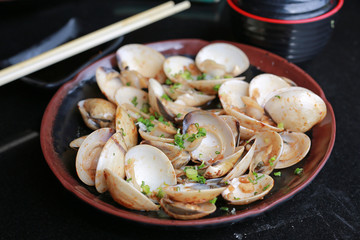 Fried Clams with spicy in plate on black table.
