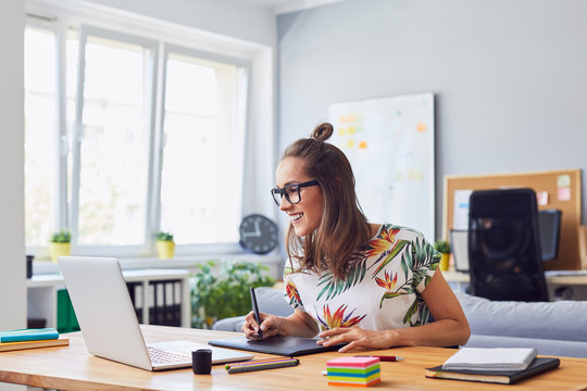 Cheerful attractive young female graphic designer smiling and working at her desk in modern office