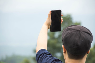people holding smartphone with nature background.
