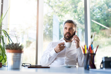 Businessman with smartphone and coffee in his office.