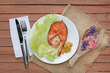 Fried salmon steak with vegetables and knife - fork on a white plate against wood plank background. Decoration with dried flower.