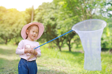 Happy little asian girl playing in a field with insect net in summer.